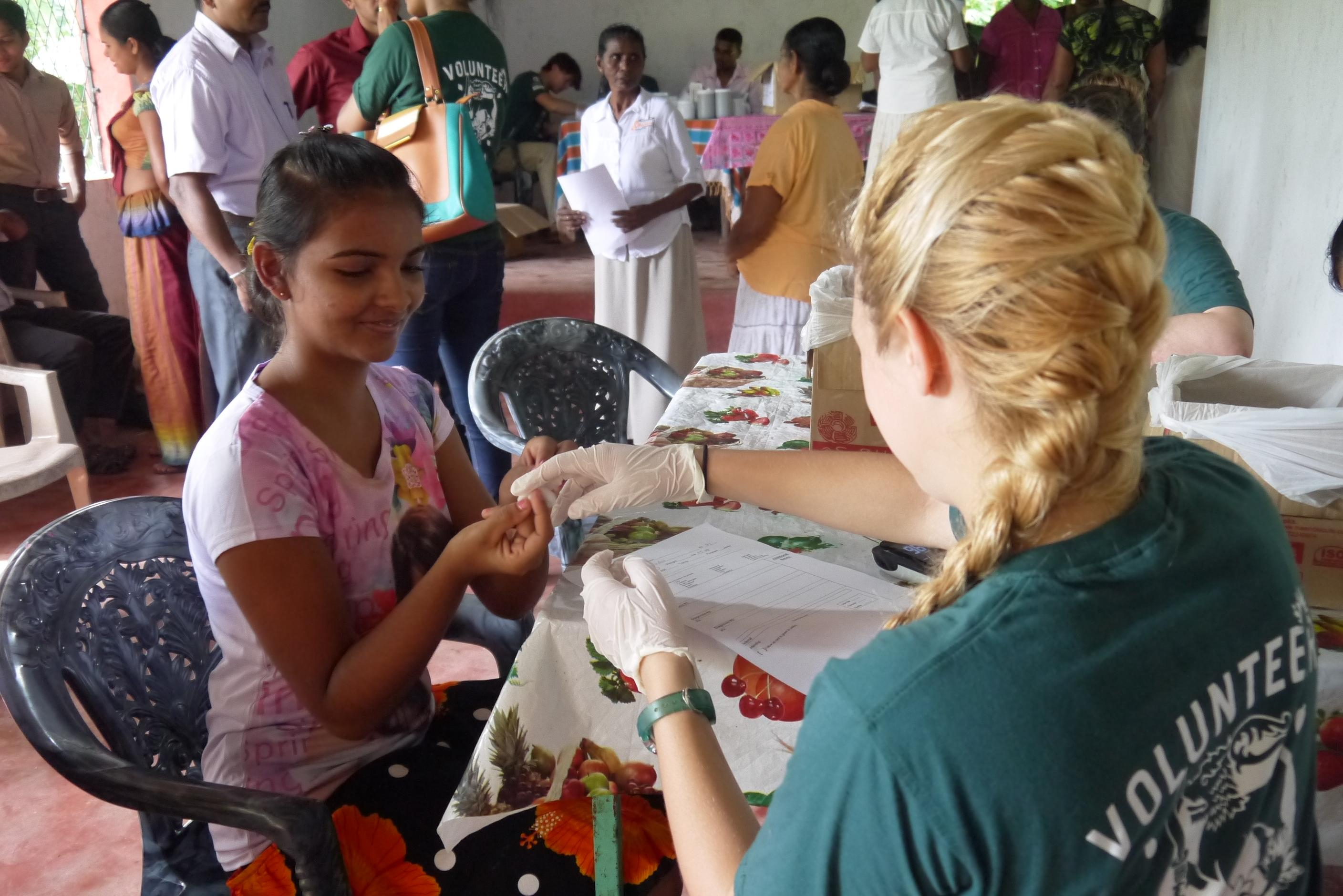 A medical internship student in Sri Lanka is pictured taking blood pressure and sugar levels at a local clinic as she gains vital work experience with Projects Abroad.